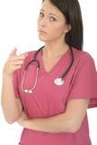 一位美丽的专业严肃有关年轻女性医生Pointing的画象失望的 免版税库存照片