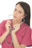一位美丽的专业严肃的年轻女性医生Putting On A Stethoscope的画象 免版税图库摄影