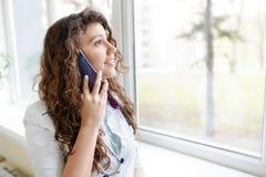 一位美丽的医生的画象谈话在电话 r 免版税图库摄影