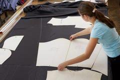 一位美丽的女孩裁缝与切口材料一起使用 库存图片