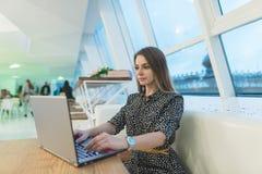 一位美丽的女性自由职业者为在一个咖啡馆的一台膝上型计算机工作与时髦的现代内部 免版税图库摄影