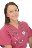 一位美丽的自然年轻女性医生Smiling的画象有听诊器的 库存照片