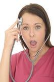 一位美丽的年轻人惊奇的女性医生与听诊器的Acting Silly的画象 库存图片