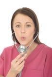 一位美丽的年轻女性医生Blowing Down A Stethoscope的画象 免版税库存图片
