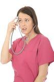 一位美丽的年轻好奇女性医生与听诊器的Acting Silly的画象 免版税库存照片