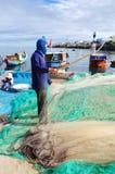 一位老渔夫在Ly儿子海岛去除鲥鱼钓鱼从他的捕鱼网开始一个新的工作日 库存照片