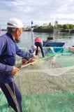 一位老渔夫在Ly儿子海岛去除鲥鱼钓鱼从他的捕鱼网开始一个新的工作日 免版税库存图片