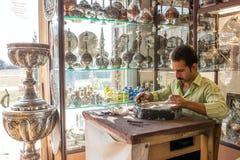 一位老熟练的工匠在一个小型作坊做传统金属纪念品 免版税库存图片
