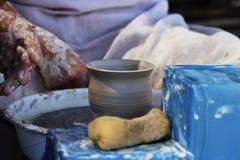 一位老练的主要陶瓷工教一个女孩转动一个罐在陶瓷工` s轮子的黏土 报告文学射击 库存图片