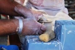 一位老练的主要陶瓷工教一个女孩转动一个罐在陶瓷工` s轮子的黏土 报告文学射击 免版税库存照片