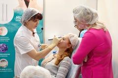 一位老练的美容师外科医生举办在邪魔的训练 免版税库存图片