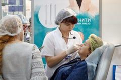 一位老练的美容师外科医生举办在邪魔的训练 免版税图库摄影