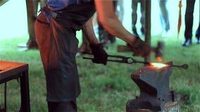 一位老练的铁匠在铁匠铺加热金属并且伪造在铁砧的熔融金属 股票录像