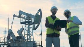 一位能学专家作指示另一个,当在油萃取站点时 石油工业,石油 股票录像