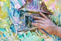 一位艺术家的手,有一把刷子的在他的手上 免版税库存图片