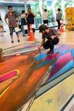 一位艺术家(托尼Cuboliquido)在图画和绘画期间他的3D艺术品。 库存照片