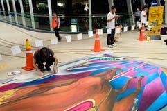 一位艺术家(托尼Cuboliquido)在图画和绘画期间他的3D艺术品。 免版税库存照片