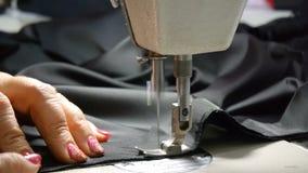 裁缝特写镜头  一位裁缝的女性手在工作 缝合与有黑材料的一台缝纫机 ?? 股票视频