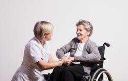 一位资深护士和一名年长妇女的演播室画象轮椅的 免版税库存图片