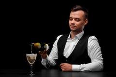 一位迷人的侍酒者用香槟填装一块玻璃,一杯在黑背景的香槟 免版税库存图片