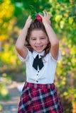 一位逗人喜爱的女小学生在手上拿着一个红色苹果,微笑对照相机 童年 教育 广告和peo的概念 库存照片