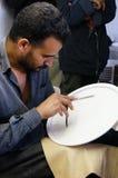 一位陶瓷艺术家在一块板材做一个设计在菲斯,摩洛哥。 免版税库存图片