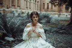 一位难以置信地美丽的公主在蕨和青苔中的城堡庭院里坐 一张美丽,害怕面孔 大哀伤 免版税库存图片