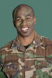 一位非裔美国人男性美国陆战队战士的画象有被伪装的面孔的在绿色背景 免版税库存照片