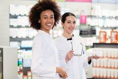 一位非裔美国人的药剂师的画象在她的同事旁边的 免版税库存照片