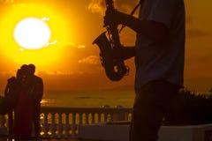 一位音乐家的剪影日落的 免版税库存照片