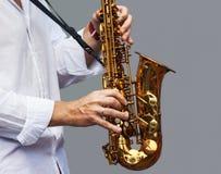 一位音乐家的手有萨克斯管的 库存照片