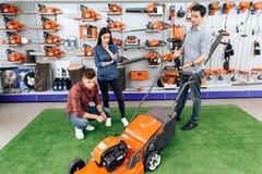 一位顾问在园艺工具商店显示一个人和一个女孩割草机 免版税库存图片