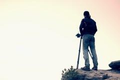 一位风景摄影师的剪影岩石峰顶的在有薄雾的谷上 图库摄影