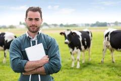 一位年轻可爱的农夫的画象在有母牛的一个牧场地 免版税图库摄影