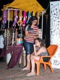 一位年轻女推销员编织另一个女孩入头发被卖的装饰品在江边的晚上在城市嗯 免版税图库摄影