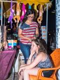 一位年轻女推销员编织另一个女孩入头发被卖的装饰品在江边的晚上在城市嗯 免版税库存图片