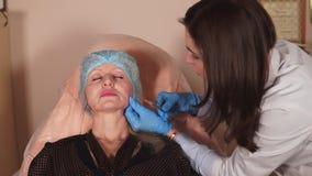 一位整形外科医生检查皮肤状况然后注射补白在皮肤下 股票录像
