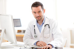 一位年轻微笑的医生的画象在他的办公室 免版税库存照片