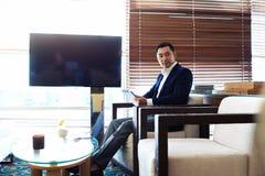 一位年轻总经理的画象有运作在触摸板的严肃的面孔的在工休期间 免版税库存图片