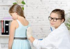 一位年轻医生审查一个女孩 库存图片