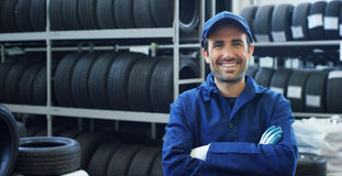 一位年轻美丽的汽车修理师的画象在一个汽车车间,在服务背景中  概念:机器修理,缺点dia 免版税库存图片