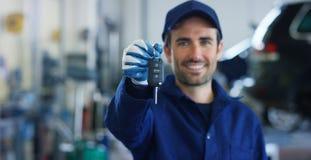 一位年轻美丽的汽车修理师的画象在一个汽车车间,在机器汽车服务概念修理的背景中,缺点 库存图片
