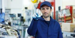 一位年轻美丽的汽车修理师的画象在一个汽车车间,在机器汽车服务概念修理的背景中,缺点 免版税库存图片