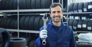 一位年轻美丽的汽车修理师的画象汽车维修车间的,有扳手的手 概念:机器修理,缺点diagnosi 免版税库存照片