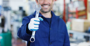一位年轻美丽的汽车修理师的画象汽车维修车间的,有扳手的手 概念:机器修理,缺点diagnosi 免版税库存图片