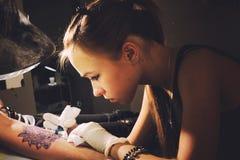 一位年轻逗人喜爱的妇女大师文身的人的画象在未来纹身花刺的藏蓝相象在手边做纹身花刺 库存图片