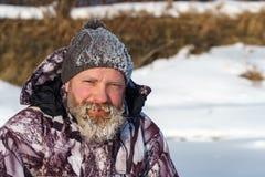 一位euriopean有胡子的渔夫人或猎人与冰和树冰在胡子看对照相机与微笑 免版税库存照片