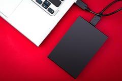 一便携式的hdd连接了到在红色背景的一台膝上型计算机 免版税库存图片