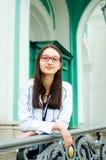 一俏丽的少女的画象戴眼镜的在一个美丽的老大厦的背景 免版税库存图片