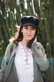 一俏丽的年轻女人的画象有黑盖帽的在仙人掌中 免版税库存照片